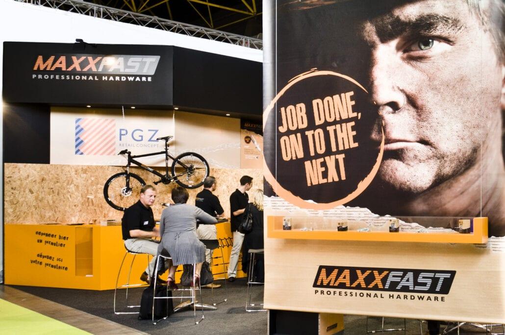 stoere foto van een werkman geprint op een banner in de beursstand van Maxxfast op DIY Homing te Kortrijk