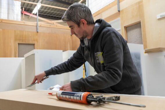 schilder plamuurt meubelstukken voor uw beursstand of interieurbouw project