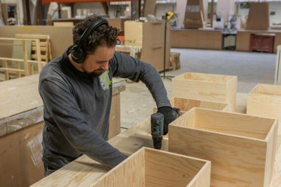 standenbouwer met een schroefmachine aan het werk aan een beursstand